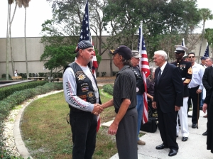 Ray Smith shakes hands with one of the Patriot Guard behind him, Cong. Bill Young greets another rider.