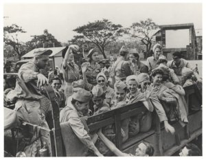 Ruby Bradley, (sitting with her arm over the side rail and waving to the camera) during the liberation of the POW camp at Santo Tomas in the Philippines during World War II. Photo courtesy AMEDD.