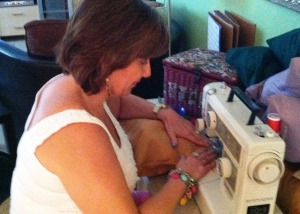 Cyd Deathe stitching closed one of 200 pillows for homeless veterans.