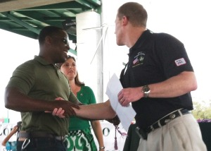 "Air Force veteran and graduating senior ""Fit"" Mangasha (left) shakes hands with Larry Braue, director of the USF Office of Veteran Services."