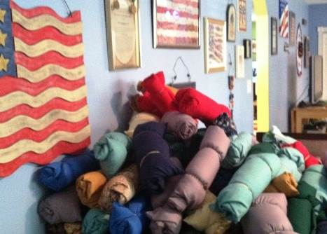 A stack of sewn, stuffed and rolled pillows waiting to be transported to the Tallahassee Stand Down for homeless veterans.