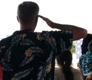 A veteran salutes during the national anthem at the USF baseball game where graduating student veterans celebrated their success.