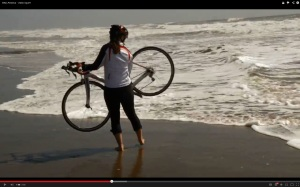 Kiersten Downs prepares to dip her rear wheel into the Pacific - a tradition for cross-country cyclists.