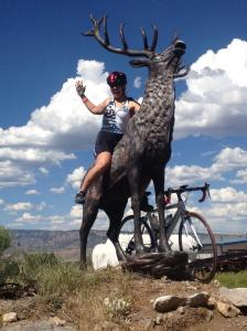 Kiersten rides an elk statute after entering Colorado on her cross country cycling tour. CREDIT: BikingUSA.net