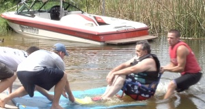 Volunteers help Navy vet Larry Binger into the water to try adaptive water skiing for the first time. Credit: Dalia Colon/WUSF Public Media