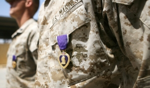 Machine gunners Cpl. Charles J. Trask, 22, and Cpl. Jimmy D. Miller, 20, with Security Platoon, Combat Logistics Company 117, Combat Logistics Battalion 7, 1st Marine Logistics Group (Fwd), stand at the position of attention with their Purple Heart awards. Trask, a Kansas City, Mo, native, and Miller, a Huntsville, Ala., native, both said that they have appreciation for their personal protective equipment.