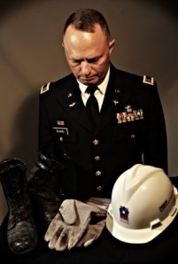 Army National Guard Chief Warrant Officer 4 Clifford Bauman examining the gloves, boots and hard hat he wore Sept. 11, 2001 trying to save lives at the Pentagon.