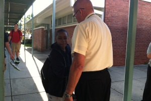 Principal Hart interacts with a student during a change in classes.