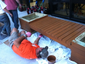Home Depot volunteer Brian Moore from store 256 paints the underside of a newly constructed bench.