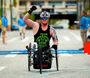 Justin Gaertner crossing the finish line - first in the 10K hand-cycling event during the 2013 National Veterans Wheelchair Games in Tampa.