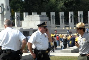 Credit Carlos Bongioanni/Stars and Stripes National Park Service security personnel speak on their phones after World War II veterans broke through a barricade with police tape that prevented access to the World War II Memorial on Tuesday, Oct. 1, 2013.