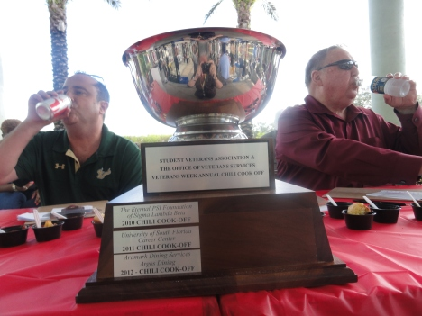 The trophy sits in between two judges who cool off their taste buds before sampling more of the chili samples from dozens of competitors at the 4th Annual USF Student Veterans Chili Cook-Off.
