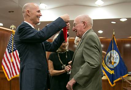 Florida Gov. Rick Scott presents a Hall of Fame medal to an unidentified inductee, Nov. 12, 2013.