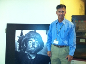 Retired Major Scott Macksam stands next to his favorite photo of the exhibition which he visited two years ago and worked to bring to the Tampa Bay area.