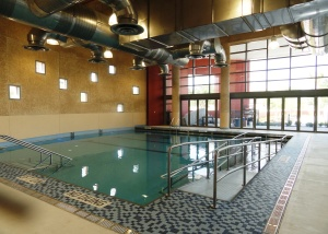 The main therapy pool that is heated by solar panels on the roof the the Polytrauma Center and the wall of doors open the pool to the outside courtyard.