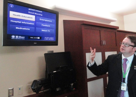Associate director David VanMeter points to the flat-screen TV that connects patients to everything from education to entertainment.
