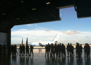 Silhouettes of Marines awaiting the ceremony frame the aircraft that brought top military leaders to the ceremony in Tampa, FL.