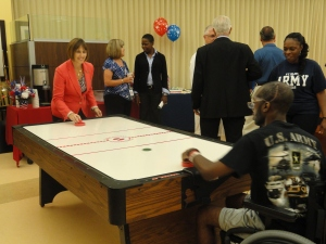 U.S. Rep. Kathy Castor (D-Tampa) plays air hockey with one of the veterans inside the new USO Day Room at James A. Haley VA Hospital.