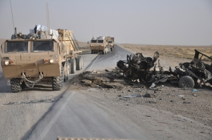A U.S. military cargo truck bypasses a charred vehicle destroyed by a roadside bomb while moving building materials to Forward Operating Base Leatherneck in Afghanistan's Helmand province, Nov. 24, 2009. Credit U.S. Army photo by Spc. Elisebet Freeburg