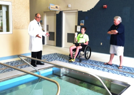 Dr. Steven Scott (left) shows off the Haley Trauma Center's treadmill pool to former patient Cory Remsburg (center) and his dad, Craig Remsburg.