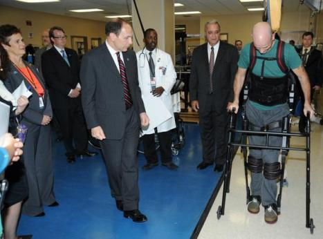 VA Secretary Bob McDonald (left) watches as paralyzed Navy Veteran Dwayne Scheuneman (right) demonstrates the Exoskeleton during the new leader's visit Wednesday at the James A. Haley VA Polytrauma Center. Credit U.S. Department of Veteran Affairs