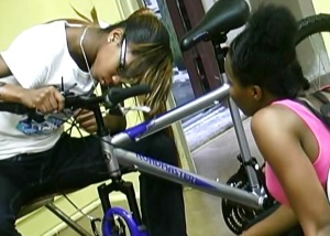 Two teens on the promotional video working to rebuild a bike.