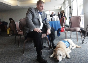 Michael Jernigan poses with his companion and guide dog for the past eight years, Brittani, at her retirement ceremony in February.