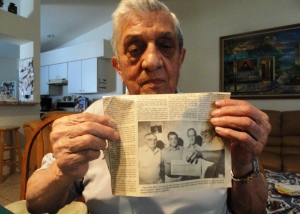 John Tedesco holds up the 1991 newspaper article that details how he and some of his friends from Erie, PA were used for mustard gas experiments while at the Great Lakes Naval Training Station in 1944.