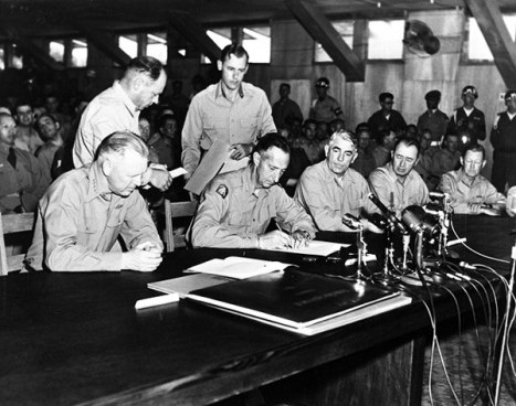 General Mark W. Clark, Far East commander, signs the Korean armistice agreement on July 27, 1953, after two years of negotiation.(U.S. Navy Museum photo)