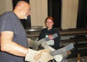 Student artist Cierra Grenier heats the steel ribbon held by Tom Monaco, professional artisan.