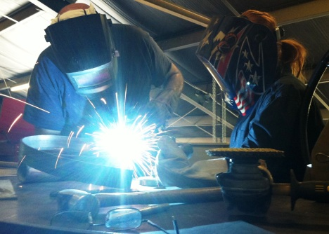 Artisan Tom Monaco spot welds two ribbons of steel together as he and student artist Cierra Grenier beginning shaping her design.