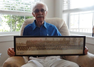 Al Boysen, 90, holds a photo of his WWII Army mobile medication unity, 139th Evac Hospital in 1945.