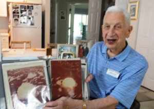 Walter Hood, 94, shows photographs he took as a 1st Lt. with the Army Air Corps of the Bikini Atoll atomic bomb tests in 1946.