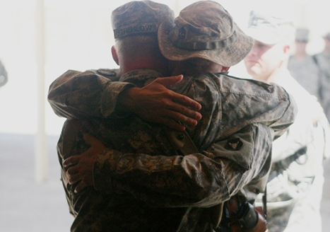 "On 4 September 2006 soldiers with Able Company, 2nd Battalion, 136th Infantry Regiment, hug during a memorial ceremony held for Army Staff Sgt. Joshua R. Hanson, a fire team leader with Able Company, at Mainside Chapel here September 4. The chapel filled with tears when a photo slide show, featuring pictures of the moments that Hanson had spent with the unit was displayed before the last roll call and a 21-shot rifle salute. The memorial consisted of the playing of our national anthem, prayer; a scripture read by Justin D. Knopf, a 24-year-old squad leader from Detroit Lakes, a photo slide show, a 21- shot rifle salute and the playing of ""Taps"". An inverted M-16A2 rifle was placed in Hanson's homage, with a Kevlar helmet resting on top. Engraved identification tags and a crucifix hung from the rifle's pistol grip. Immediately in front, an empty pair of boots was positioned, while behind the display, the national ensign and battalion colors were displayed. Along the sides were two ammunition cans containing keepsakes from fellow soldiers. The battalion, an Army National Guard unit out of Detroit Lakes, Minn, is currently attached to 1st Marine Logistics Group (Fwd). Able and Headquarters Companies, 2nd Battalion, 136th Infantry Regiment, 1st Marine Logistics Group is deployed with I MEF (FWD) in support of Operation Iraqi Freedom in the Al Anbar Province of Iraq (MNF-W) to develop the Iraqi Security Forces, facilitate the development of official rule of law through democratic government reforms, and continue the development of a market based economy centered on Iraqi Reconstruction. (U.S. Marine Corps photo by Lance Corporal Ryan L. Tomlinson)"