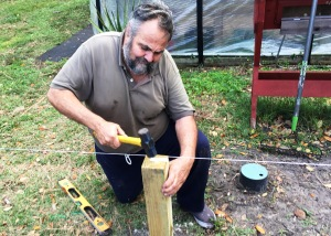 Vietnam veteran Bernie Lodico hammers in a post for the fence surrounding the Veterans Garden.