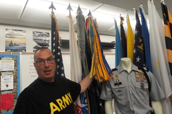 JROTC retired Army Lt Col Mo Bolduc shows the display of ribbons and flags that adorn the JROTC room and computer lab